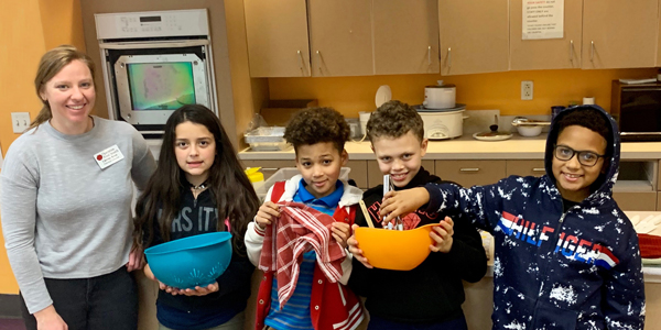 Young volunteers learning to cook