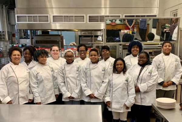 High school students serving as nutrition ambassadors wear chef coats.